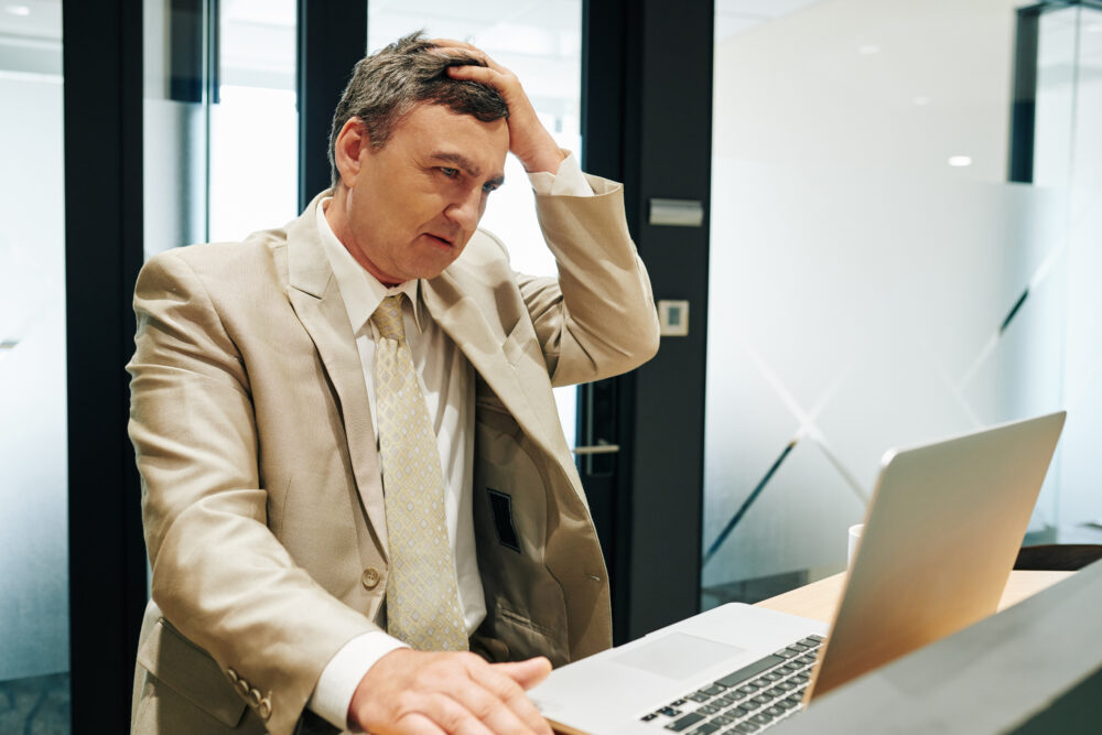 a businessman having problems with his computer due to a cyber attack